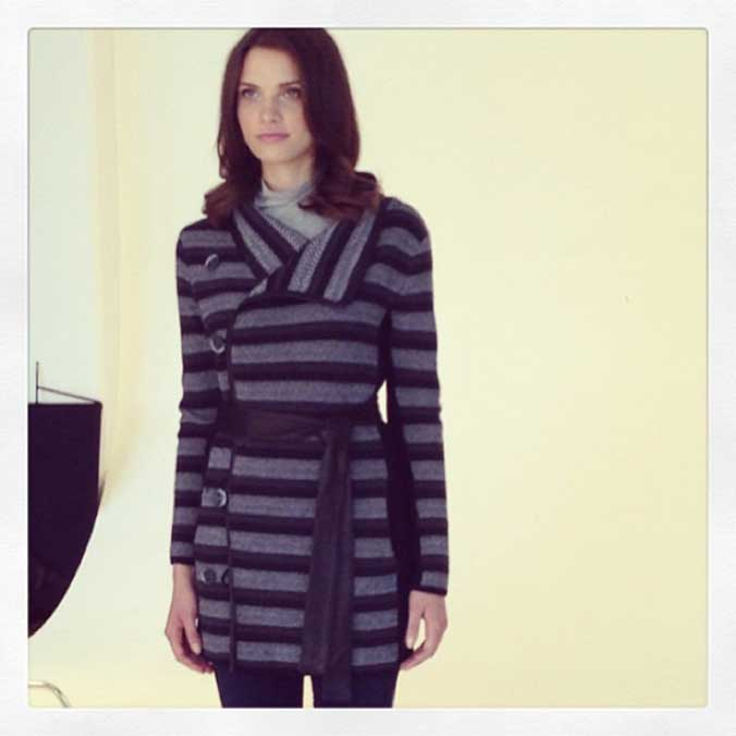 Model in a photo studio, wearing a dark and light grey horizontally striped cashmere sweater